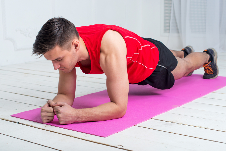 fitness training athletic sporty man doing plank exercise in gym