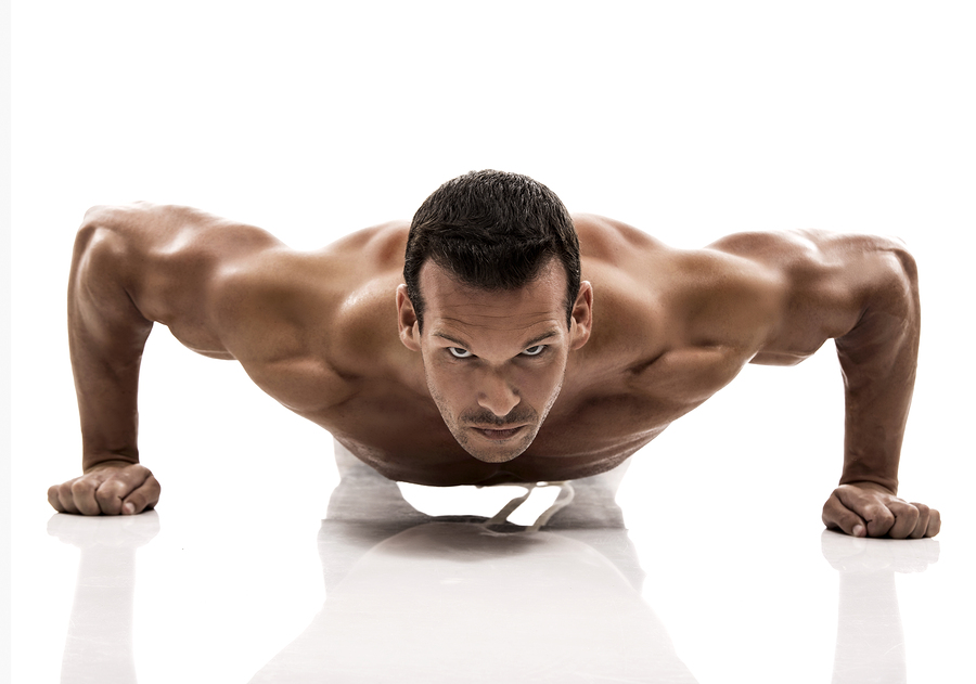 Muscle man dmaking push ups in studio, isolated over a white bac